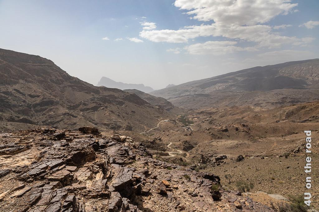 Auf dem Weg zum Jebel Shams - Ausblick in ein Seitental. Im Bild sieht man ein hügeliges Tal, durch welches sich ein Weg an der linken Seite schlängelt. Im Hintergrund erhebt sich ein spitzer Berg im Dunst.