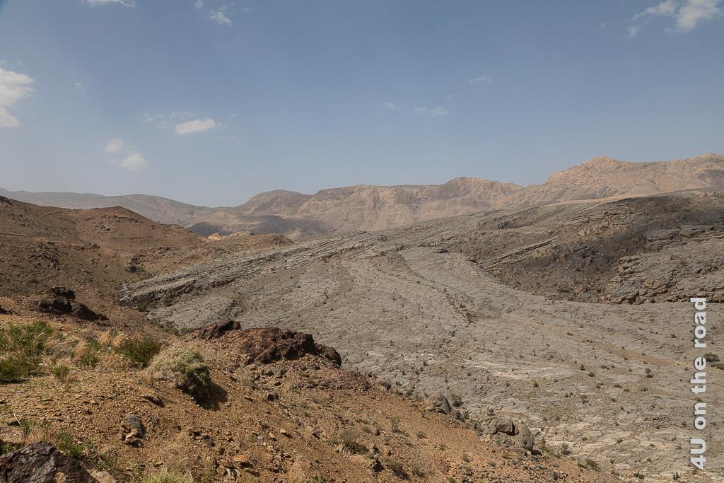 Auf dem Weg zum Jebel Shams - faszinierende Felsen. Im Bild sieht man wie sich ein schräges Plateau aus hellerem Gestein in braune Steine ergiesst. Im Hintergrund erhebt sich eine Bergkette.