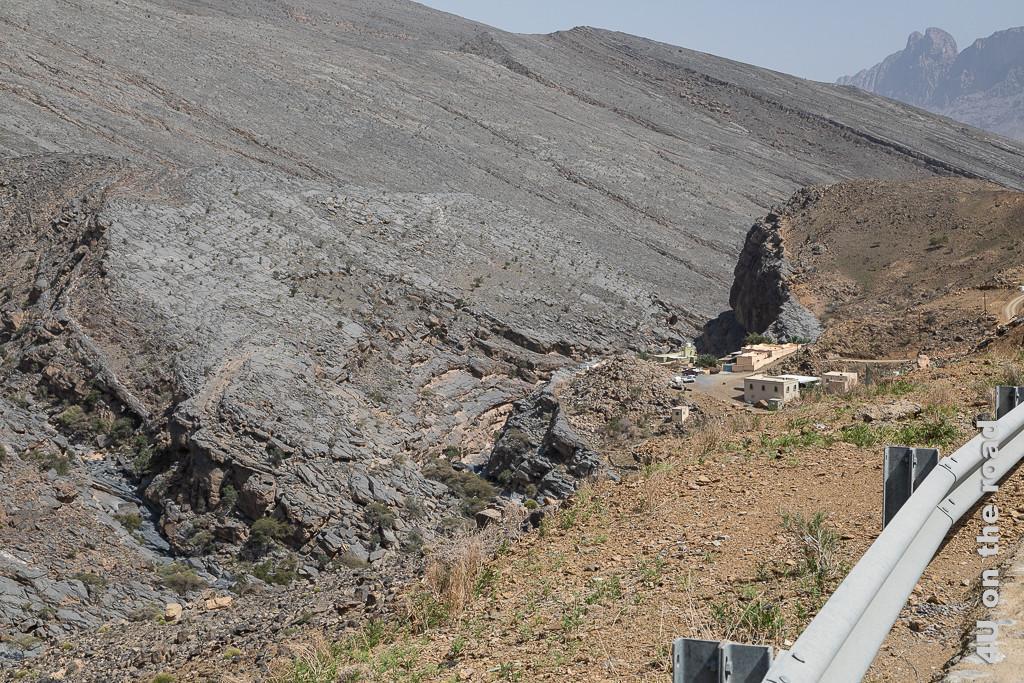Selbst in dieser schroffen Felswelt stehen Häuser. Im Bild sieht man ein massives Felsplateau im 45 Grad Winkel geneigt. Es stösst an eine andere Gesteinsschicht. Im schmalen Tal befindet sich ein trockenes Flussbett. An einem Felsvorsprung wurden mehrere Häuser gebaut.