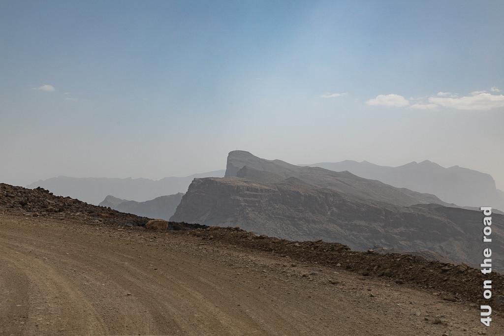 Auf dem Weg zum Jebel Shams - Auf der Gravelroad in luftiger Höhe. Das Bild zeigt die Strasse, auf deren rechten Seite es tief nach unten geht. Weiter hinten erheben sich Berge im Dunst.