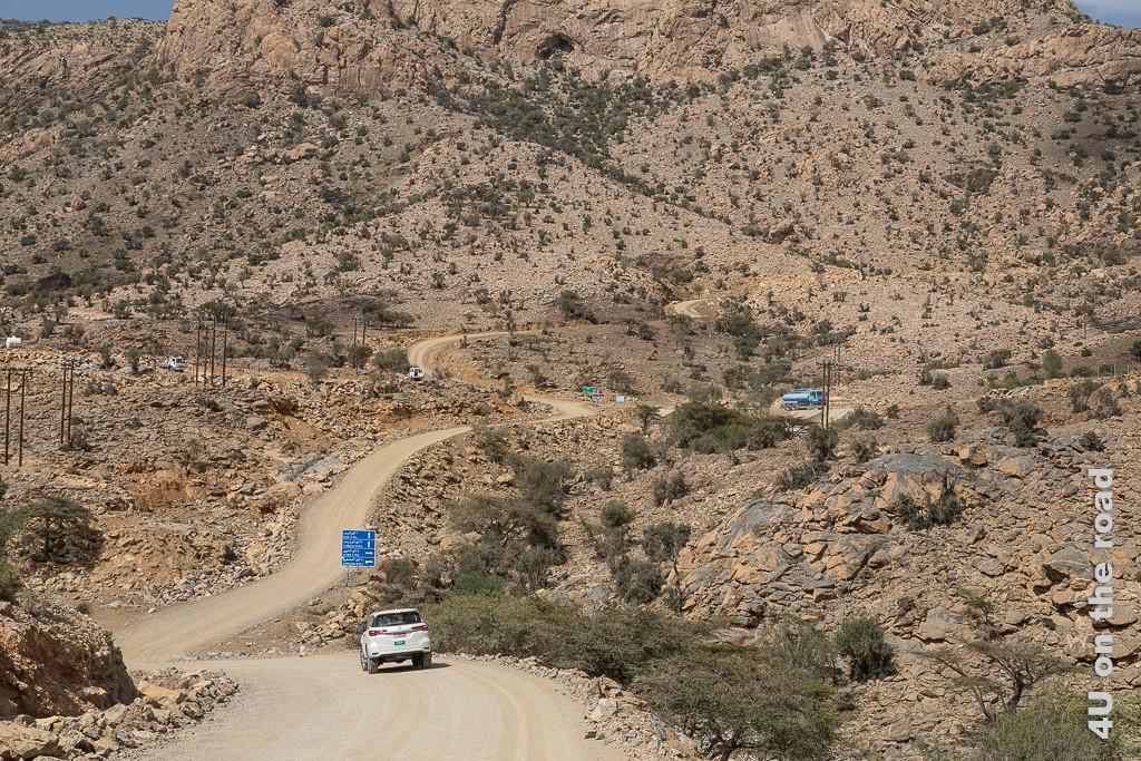 Auf dem Weg zum Jebel Shams - Ganz schön was los unterwegs. Den blauen Tanklaster dürfen wir später überholen. Im Bild sieht man die sich verzweigende Gravelroad, blaue Wegweiser, zwei weisse LKWs, den blauen Tanklaster und einen 4 x 4 Toyota.