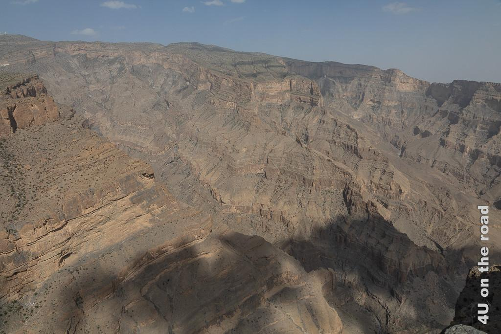 Ausblick auf das Ende der Wadi Nakhar Schlucht. Im Bild sieht man die steil abfallenden Felsen mit Felsvorsprüngen und Verwitterungen.