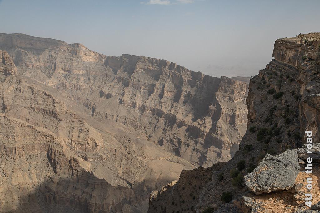 Blick in die Felswelt oberhalb der Wadi Nakhar Schlucht. Geneigte Felsen mit durch Verwitterung entstandenen Vorsprüngen fallen zum Tal steil ab. Auf der rechten Seite verhindert ein steiler Felsvorsprung den Blick ins Tal