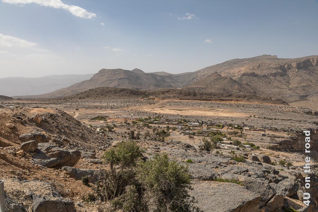 Hochplateau oberhalb der Wadi Nakhar Schlucht. Das Hochplateau ist bewohnt, auch gibt es mehrere Hotels hier oben. Im Bild sieht man im Hintergrund hohe Berge, das von der Strasse zerschnittene trockene Hochplateau mit einzelnen Bäumen und Häusern.