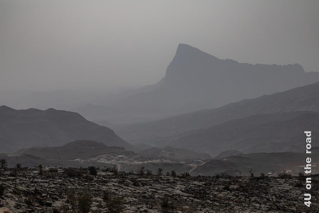 Abendstimmung auf dem Rückweg. Im Bild sieht man einen Ort umgeben von Bergen im Dunst, wobei ein Berg mit einer Spitze markant in den Himmel ragt