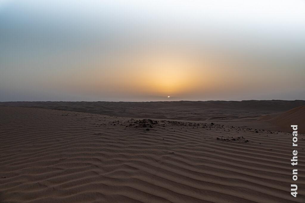 Die Sonne klettert über den Horizont in der Wahiba und offenbart das Wellenmuster im Sand