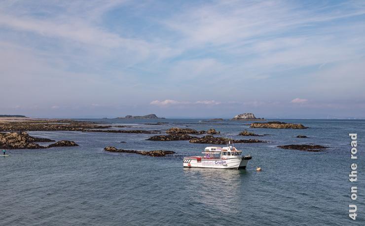 Die Küste von North Berwick mit Felsen im Wasser und dem kleinen Seabird Cruise Schiff
