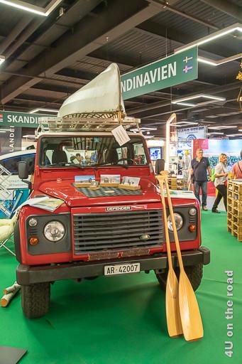 Alter Defender mit Leichtbau-Kanu auf dem Dachträger, die Paddel lehnen an der Motorhaube, Suisse Caravan Salon Bern