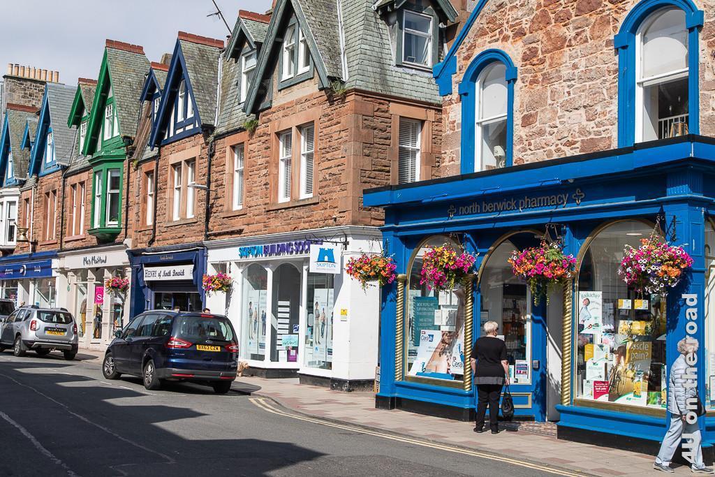Einkaufsstrasse von North Berwick. Im Bild farbige Geschäftsfassaden und bunte Blumenkörbe