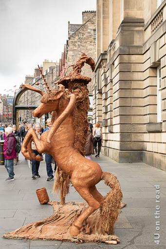 Strassenkünstler mit Einhorn auf der Royal Mile in Edinburgh. Das Einhorn steht auf den Hinterbeinen und der Zauberer schwebt scheinbar in der Luft.