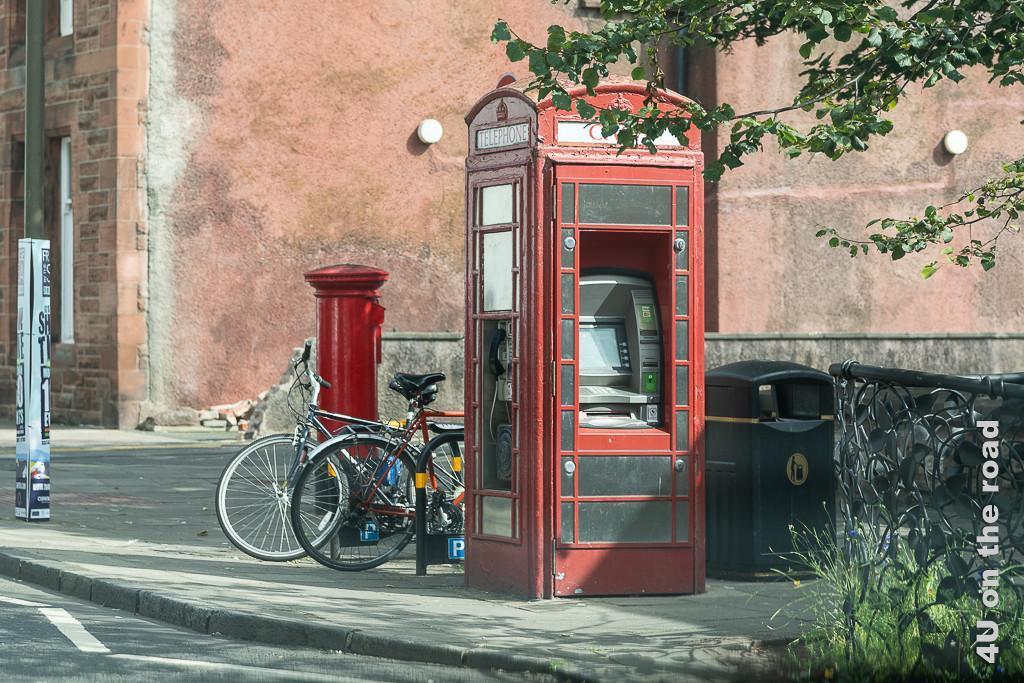 Telefonzelle als Multitalent in North Berwick. Die abgebildete Telefonzelle ist Bankautomat und Telefonzelle. Dahinter befindet sich ein Fahrradparkplatz und ein Briefkasten