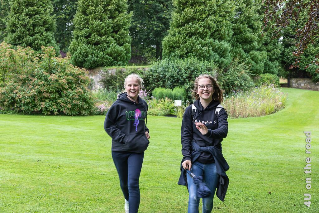Die Mädchen nutzen den Park von Falkland Palace für einen Wettlauf. Im Vordergrund die rennenden Mädchen, im Hintergrund Blumenrabatten und Bäume.