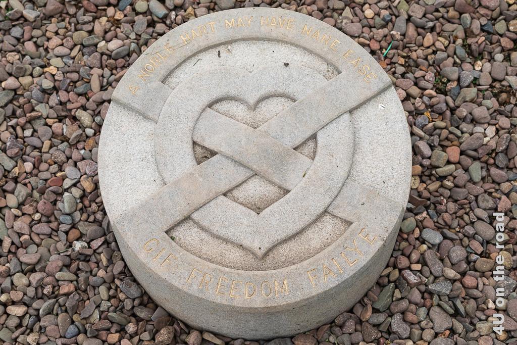 Melrose Abbey - Begräbnisstätte des Herzen von Robert the Bruce im Garten von Kloster Melrose. Ein weisser, runder Stein mit Herz, durch welches zwei Bänder über Kreuz geschlungen sind, markiert die Stelle.