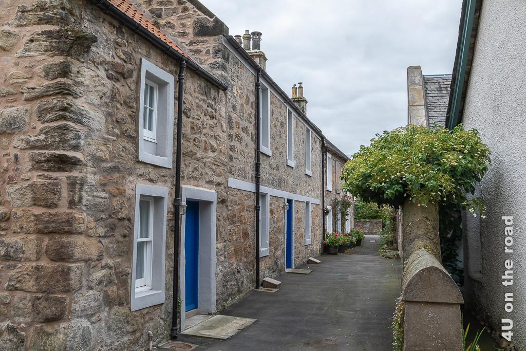 Schmaler Weg mit restaurierten, winzigen Reihenhäusern mit 2 Etagen in Culross. Die blauen Haustüren bieten einen tollen Kontrast