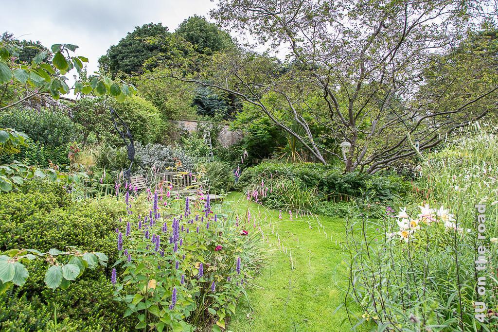 Hinter der grossen Mauer im privaten Garten in Culross. Im Blick ein geschützter Sitzplatz an der Mauer mit Skulptur, der von Rabatten und Bäumen umgeben ist.