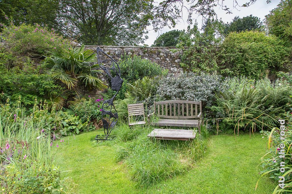 Sitzplatz hinter der Mauer im privaten Garten aus der Nähe. Eine Holzbank mit einem flachen Tisch davor und einem Klappstuhl laden ein zum Verweilen.