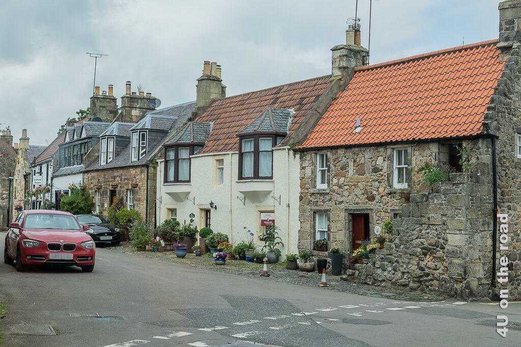 Cottages in Falkland. Im Bild sieht man winzige Cottages mit 2 niedrigen Etagen. Alle Häuser sind aneinander gebaut. Manche Häuser wurden bei der Renovation verputzt. Überall stehen liebevoll bepflanzte Blumentöpfe.