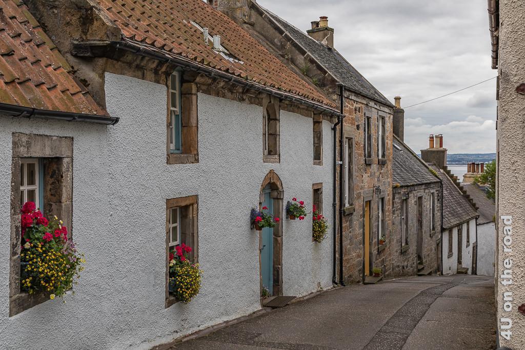 Schmaler Weg, der von der Kirche runter ins Dorf führt. Rechts und links stehen kleine restaurierte Häuschen