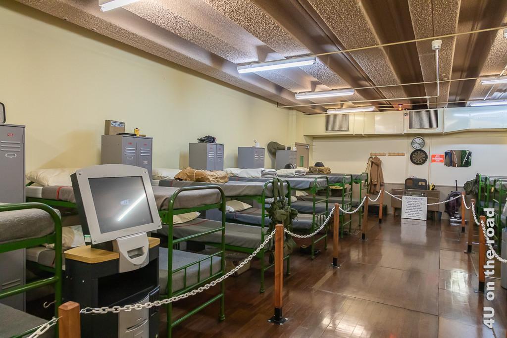 Schlafräume der normalen Angestellten Secret Bunker . Im Bild sieht man 6 Doppelstockbetten nebeneinander und vis-a-vis, getrennt durch Doppelspinde. Im Vordergrund steht ein uralter PC.