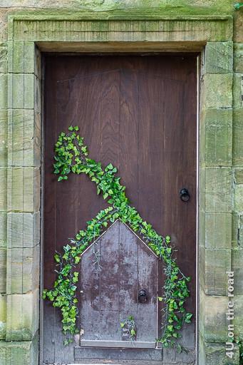 Alnwick Gardens Tor in der Mauer des Formalen Gartens von der anderen Seite. Die Tür ist Braun. Die Miniaturtür ist von Efeu umrankt.