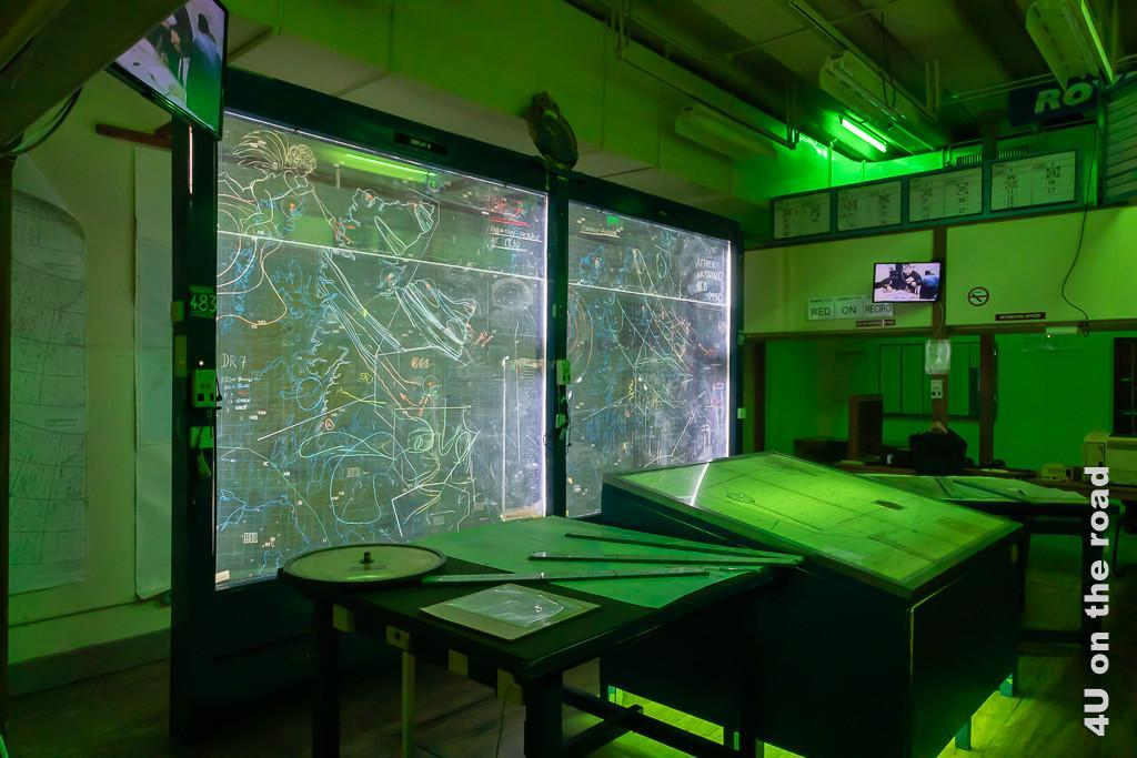 Arbeitsraum des Planungsstabs im Secret Bunker. Modern erscheinende Boards und grosse Arbeitsflächen mit Linealen zur Koordinatenbestimmung beherrschen den in grünes Licht getauchten Raum.