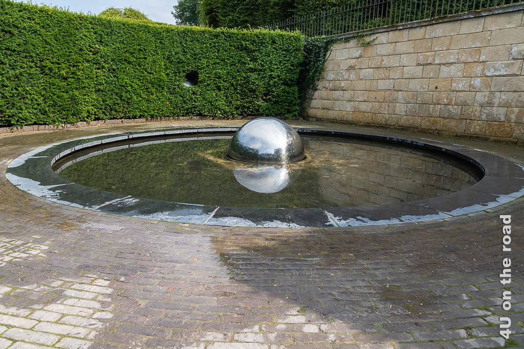 Alnwick Gardens - Wassergarten - Teich mit Kugel. Das Wasser rinnt über die Edelstahlkugel, die den Himmel und sich selbst im Teich spiegelt