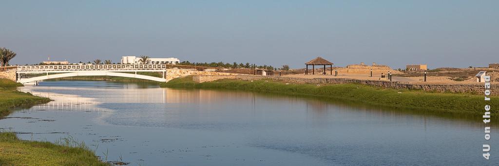Al Baleed - Brücke über die Lagune zur Ausgrabungsstätte. Im Bild zu sehen sind Teile der Ausgrabung, die weisse Brücke und die Lagune