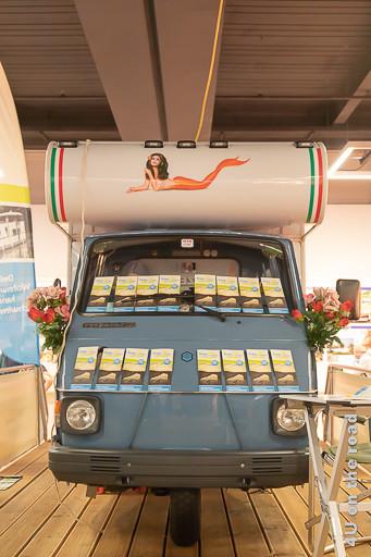 Werbung der Firma Freecamper für ihr Floss auf dem Suisse Caravan Salon. Im Bild sieht man ein altes Fiat Piaggio Wohnmobil.