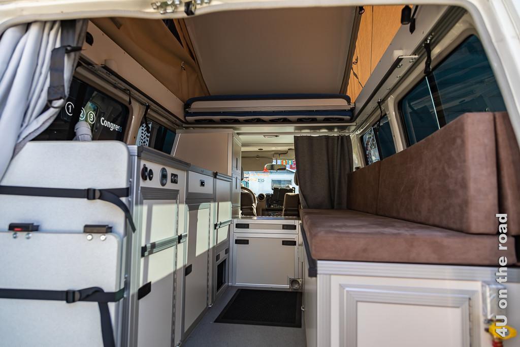 Ein Van als Wohnmobil auf dem Suisse Caravan Salon Bern von Innen, oben sieht man das hochgeklappte Dach und das zusammengeschobene Bett. Unten sind Küchenmodule in Kastenform verbaut.