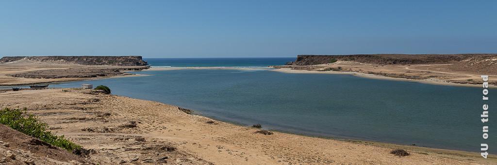 Lagune Khor Rori von der antiken Hafenstadt Sumhuram aus gesehen. Im Bild sieht man den Sandstreifen zwischen Lagune und Meer gerahmt von zwei Felsen. Links sind Boote zu sehen.