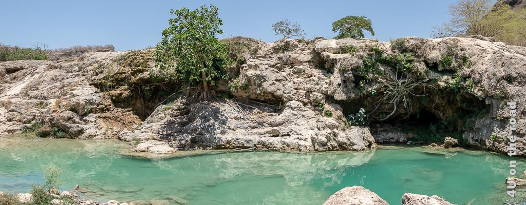 Wadi Darbat - im Bild türkis farbenes Wasser, bewachsene Kalksteine und ausgewaschene Höhle.