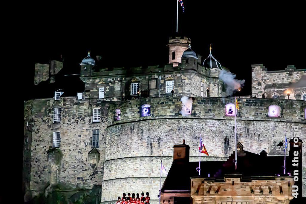 Salut Schüsse zum Beginn des Military Tattoo vom Edinburg Castle. Im Bild sieht man die beleuchteten Kanonen und Rauch.