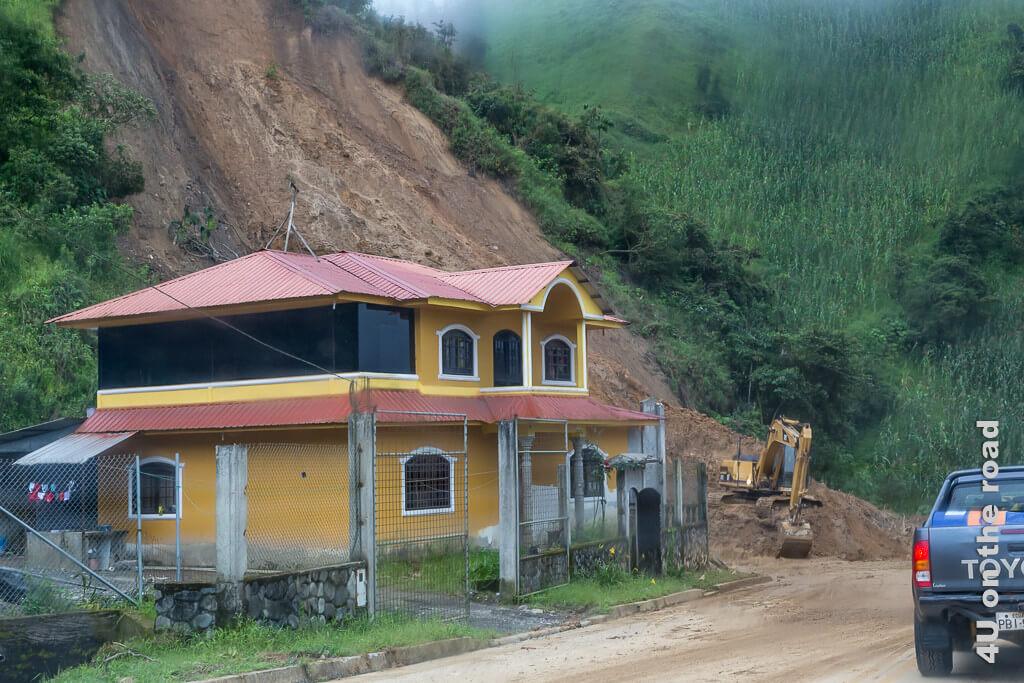 Erdrutsch in Ecuador - die Hausbewohner haben viel Glück gehabt. Die Strasse ist bereits wieder freigeräumt. Illustration mit dem Mietwagen in Ecuador unterwegs.
