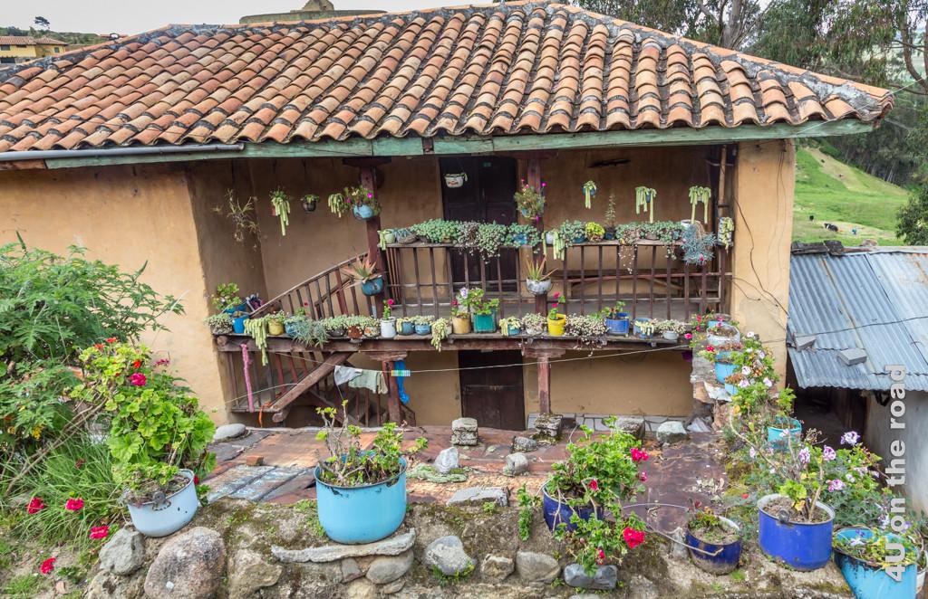 Haus dekoriert mit lauter bepflanzten alten Emailletöpfen