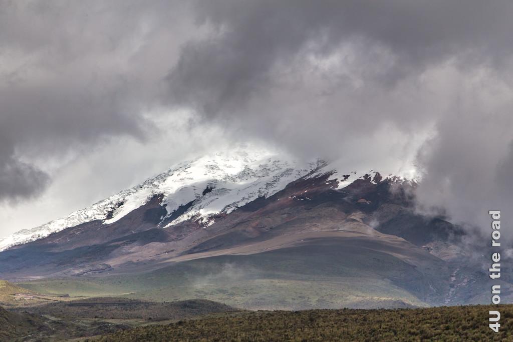 Die Wolkendecke am Cotopaxi Vulkan reisst kurz auf und lässt das rote Dach des Refugio José Rivas erkennen