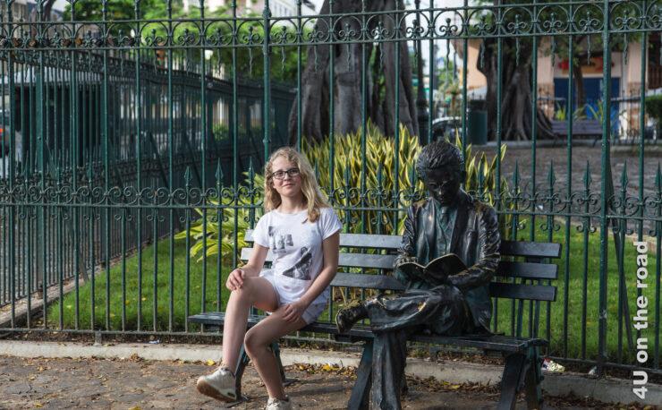 Parkbank mit lesender Bronze Skulptur und Mädchen