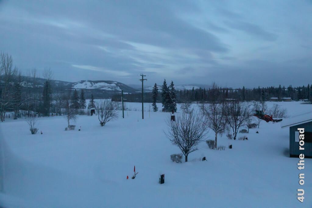 Im ersten Grau des Tages werden wir vom Schneepflug geweckt. Blick aus dem verschneiten Fenster des Carmack Hotels.