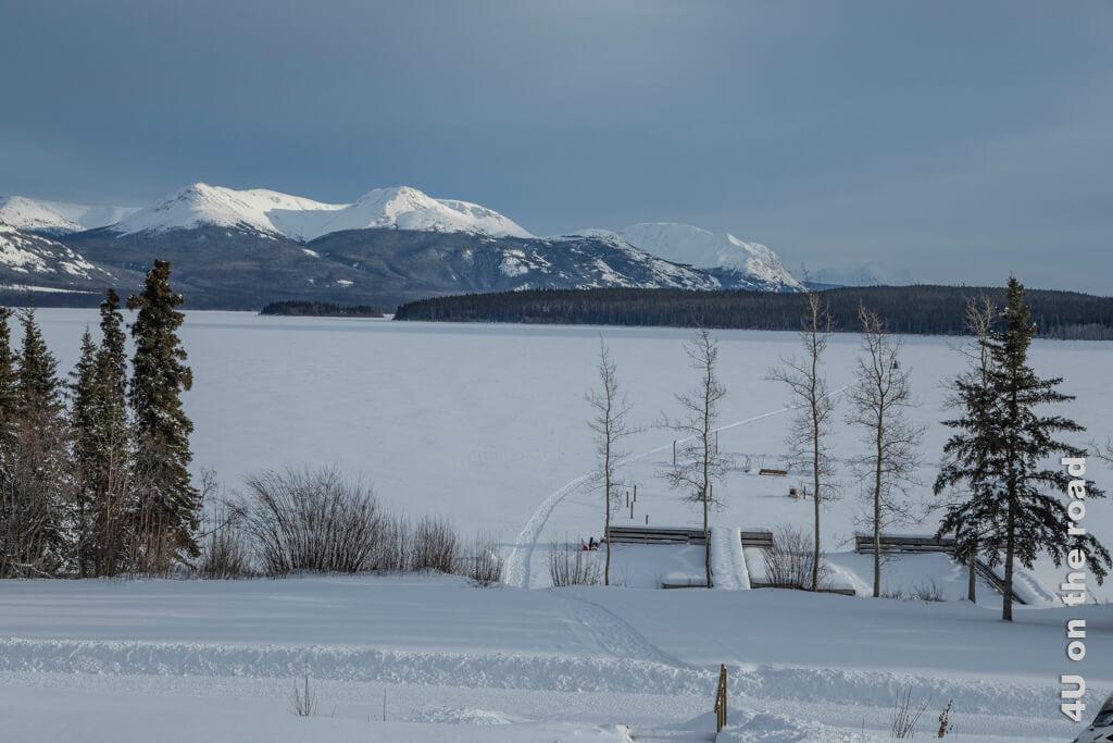 Vom Restaurant werfen wir einen letzten Blick zurück auf den Tagish Lake und das Bergpanorama. Der Himmel bestätigt die Wettervorhersage, nach der es weiteren Schnee gibt.
