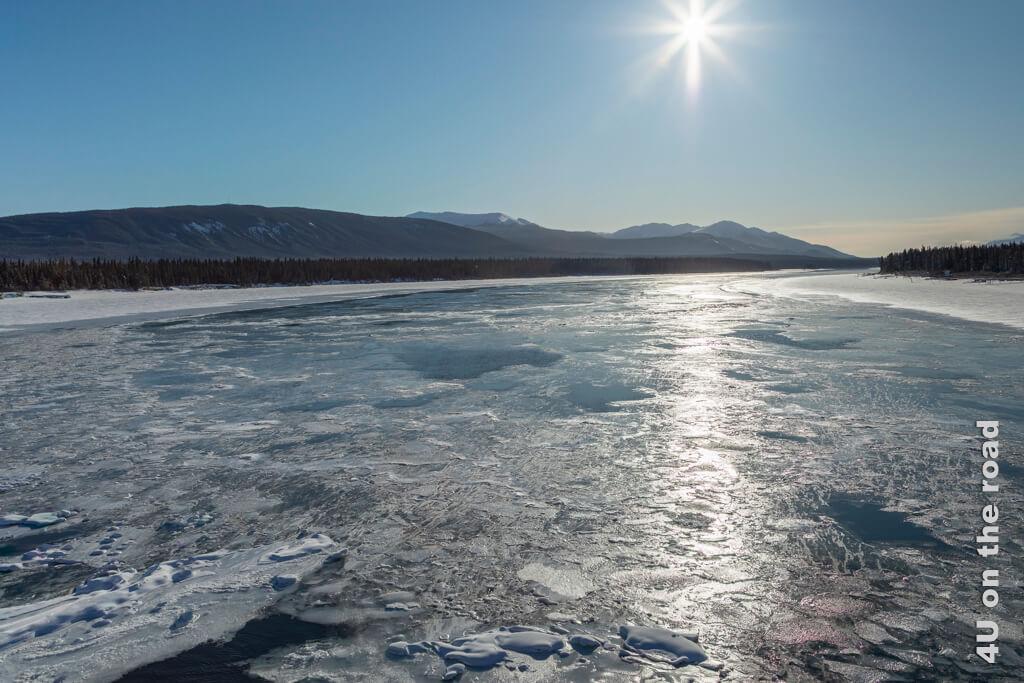 Die Eisschollen auf dem Tagish River glänzen im Gegenlicht. Die Windrichtung ist auch gut zu erkennen.