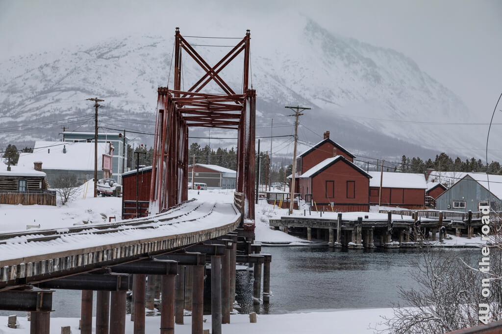 Eisenbahnbrücke und Eisenbahndepot Carcross von der gegenüberliegenden Flussseite aus gesehen