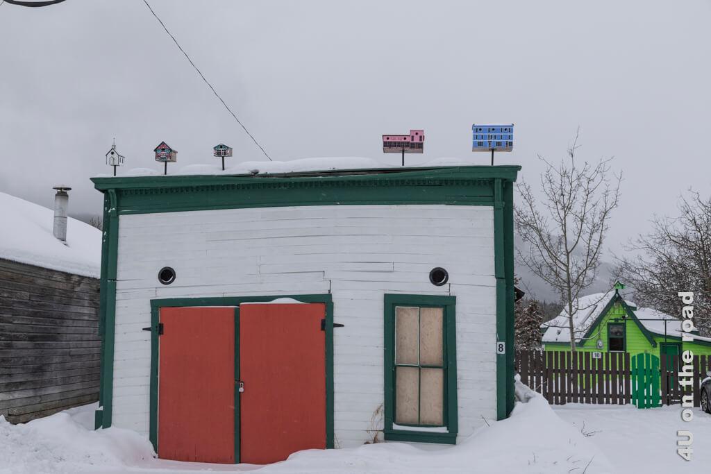 Originale Miniaturhäuser nach Häusern in Carcross auf dem Dach des Schuppens und hellgrün daneben die Tommy Brooks Cabin