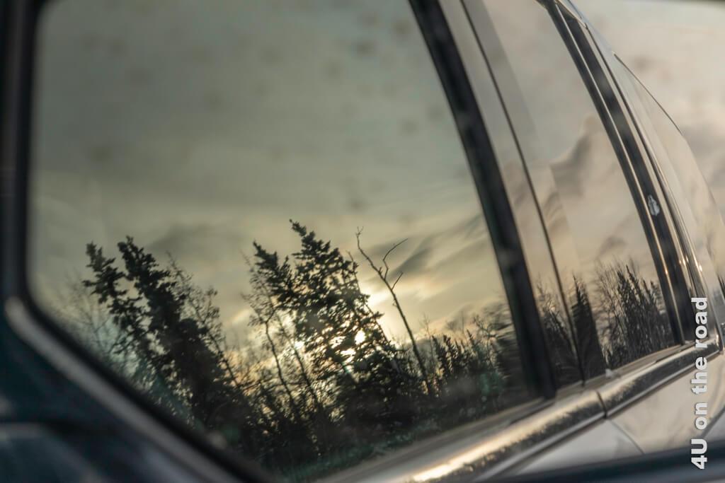 Die aufgehende Sonne spiegelt sich in den Scheiben des Autos