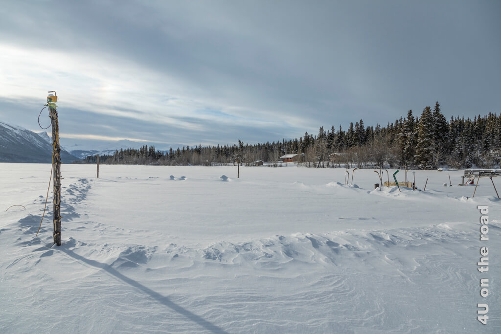 Verschneites Eishockey Feld auf dem Tagish Lake angeleuchtet von den letzten Strahlen der untergehenden Sonne