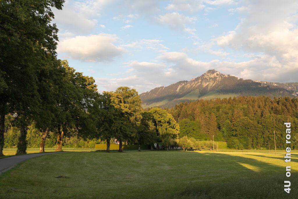 Sicht auf von der Abendsonne angeleuchtete Berge bei einem Abendspaziergang in Bulle