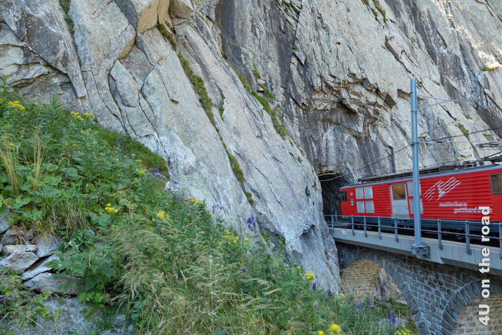 Ein Zug der Matterhorn-Gotthard-Bahn fährt in den Bahntunnel bei der Schöllenenschlucht ein