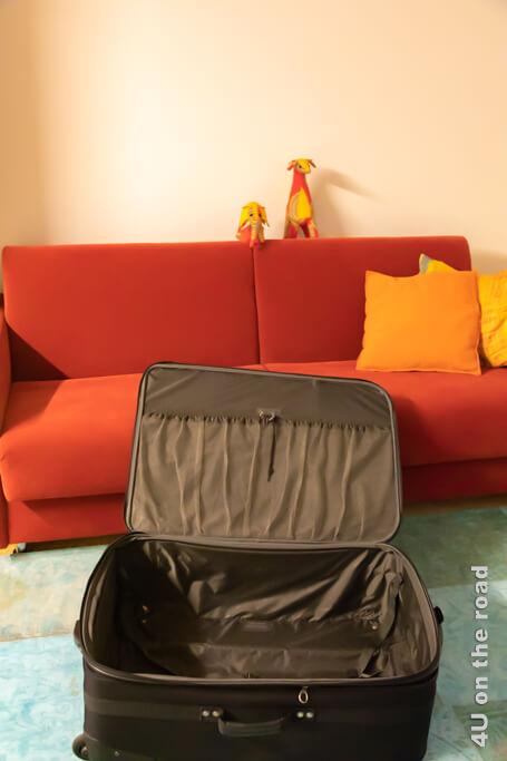 Erwartungsvoll starrt mich der noch leere Koffer im Keller an. Auf dem Sofa sammeln sich noch keine Sachen. - Koffer packen für das Austauschjahr