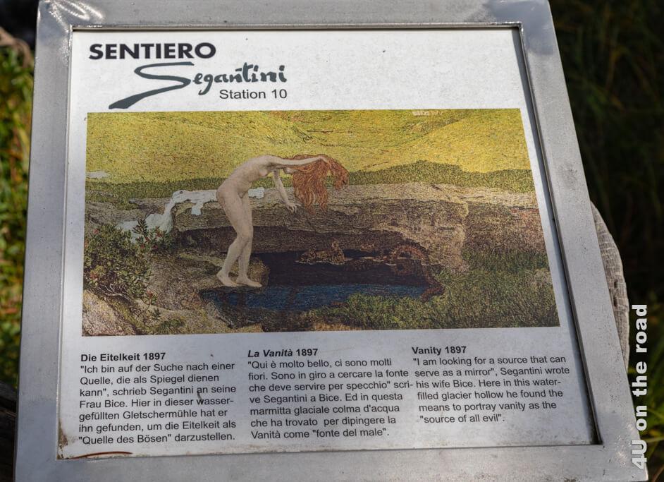 """Hinweistafel auf dem Sentiero Segantini mit dem Bild """"Eitelkeit"""" von Giovanni Segantini"""