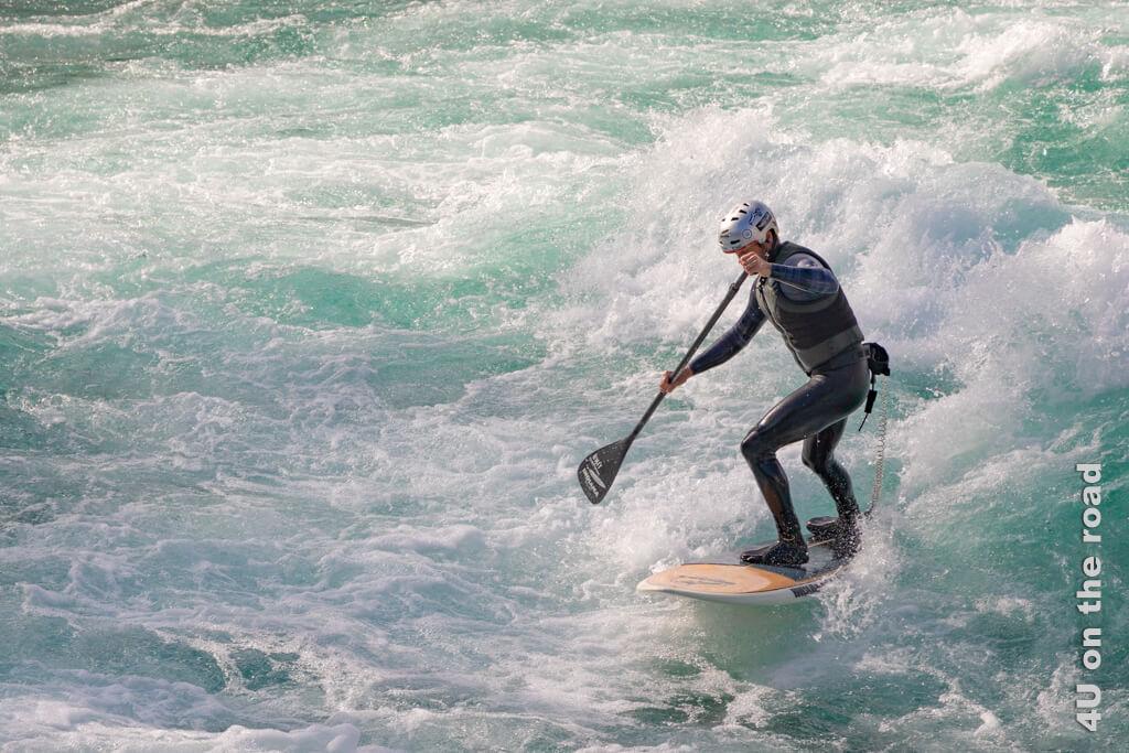 Hier übt jemand ein Mittelding zwischen Standup Paddling und Surfen in der Aare. Mit dem Paddel navigiert er sich immer wieder in die Strömung.