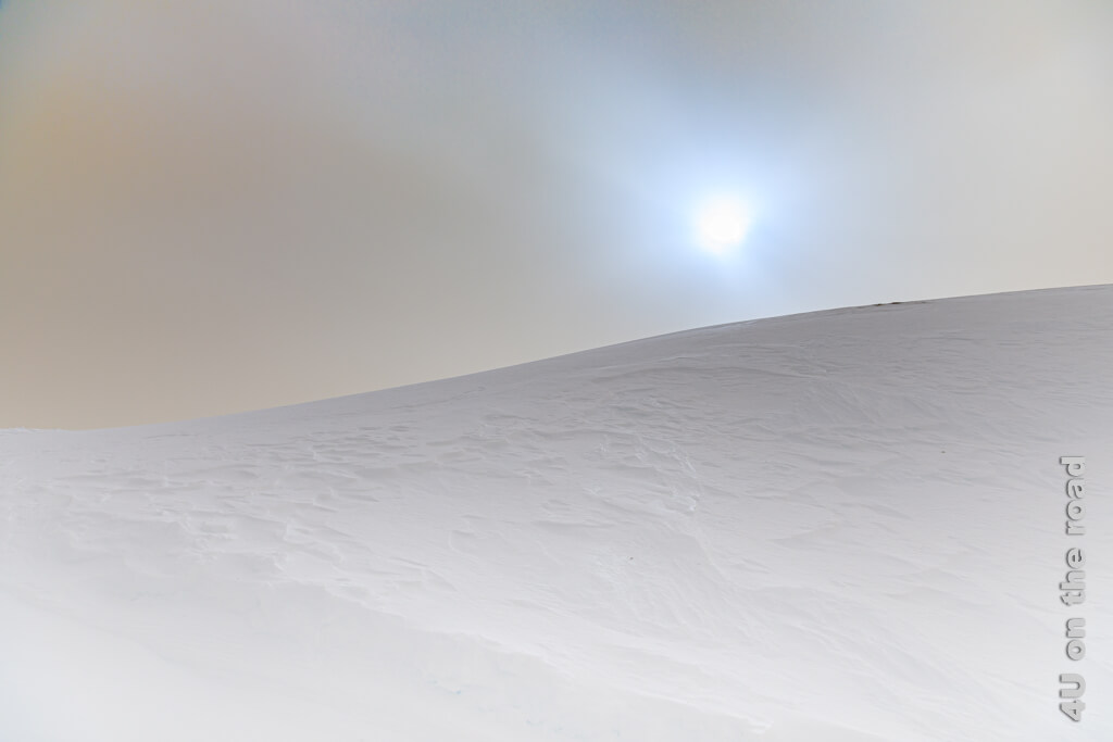 Der Schnee verwandelt die Berge in eine Dünenlandschaft. Der in der Atmosphäre schwebende Sahara-Staub setzt eigene Akzente. Winterwanderung auf dem Pizol