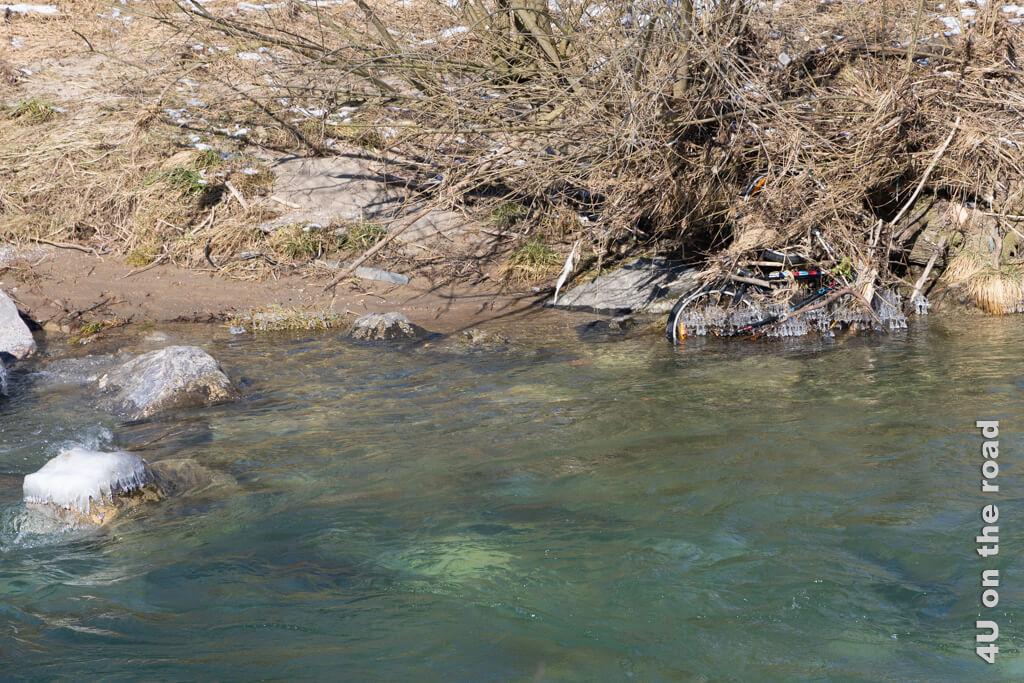 Vom anderen Ufer erkennt man ein im Busch verfangenes auffälliges Fahrrad, welches sich mit Eis geschmückt hat.